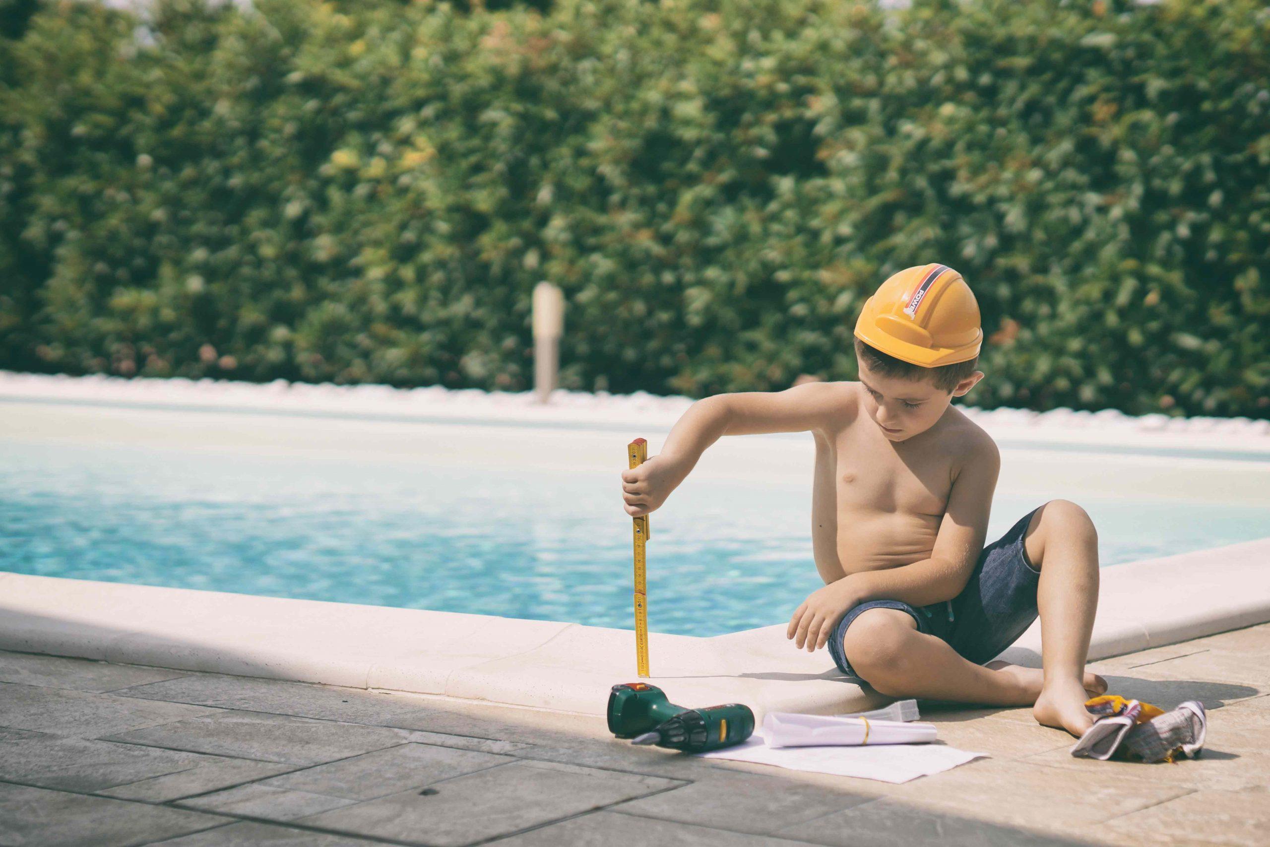 foto di un bambino seduto sul bordo di una piscina esterna